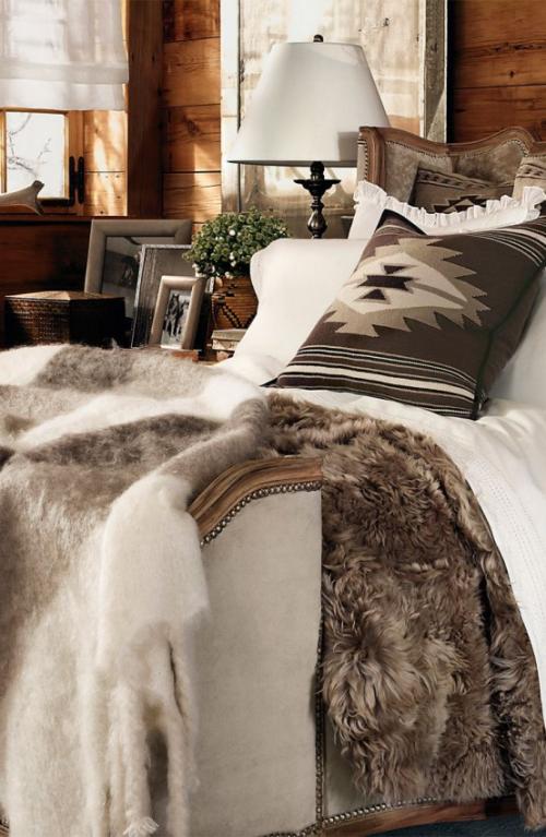 Gemütliches Schlafzimmer im Winter gestalten Beige und Braun weißer Hintergrund Kissen mit Ethno-Muster Kunstfell Lampe