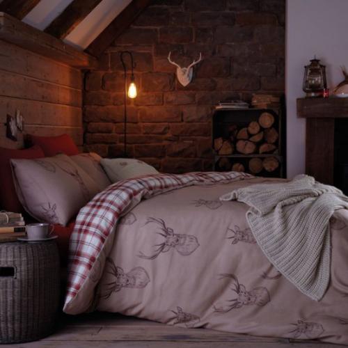 Gemütliches Schlafzimmer im Winter gestalten Brennholz Hängelampe dezentes Licht unter der Dachschräge