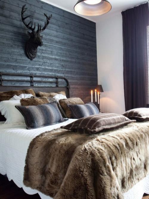 Gemütliches Schlafzimmer im Winter gestalten Decke Kunstfell beige weiße Bettwäsche Hirschgeweih