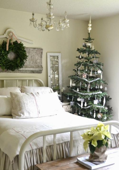 Gemütliches Schlafzimmer im Winter gestalten großer Schlafbett weiß-cremige Bettwäsche kleiner Christbaum daneben Weihnachtsstern Kranz