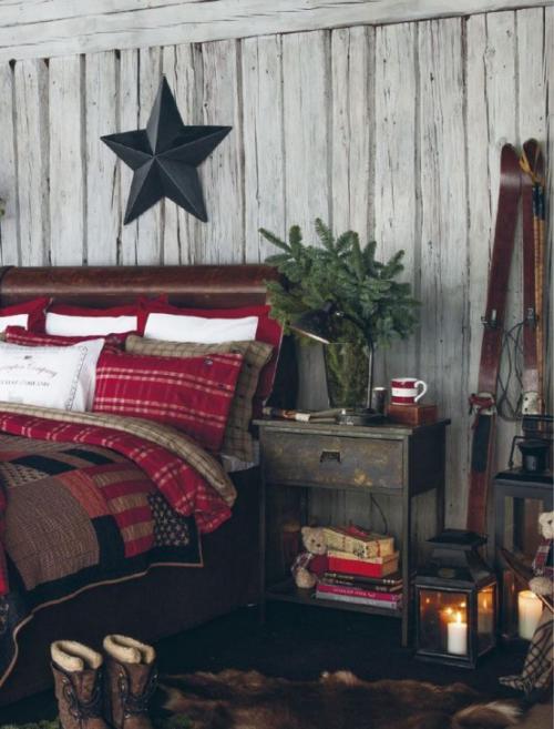 Gemütliches Schlafzimmer im Winter gestalten rustikales Ambiente Stern aus dunklem Holz Holzwand buntes Bettzeug
