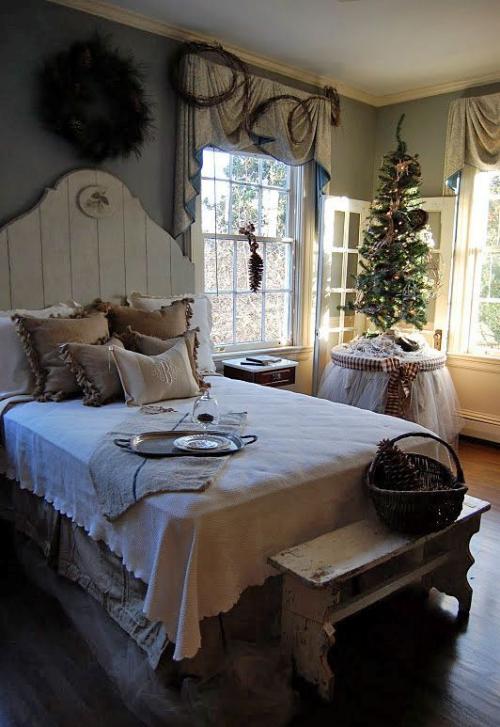 Gemütliches Schlafzimmer im Winter gestalten rustikales Ambiente kleiner Christbaum in der Ecke vor dem Fenster