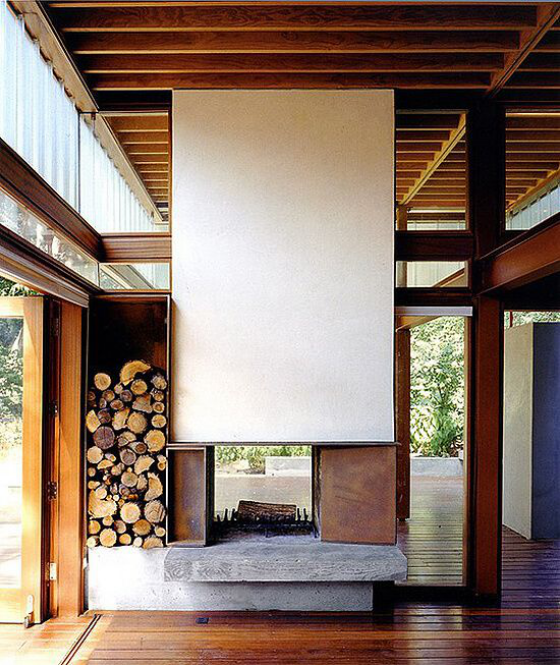 Moderne Kamine doppelseitiger Kamin Brennholzregal daneben Hartholzboden Holzdecke
