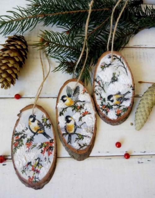Rustikale Weihnachtsdeko bamalte Holzscheiben mit bunten Vögeln darauf
