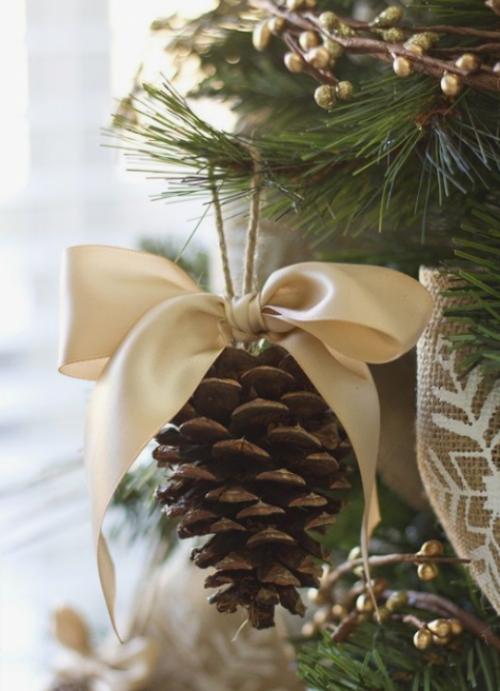 Rustikale Weihnachtsdeko selber machen Tannenzapfen mit einer cremefarbenen Schleife für den Christbaum