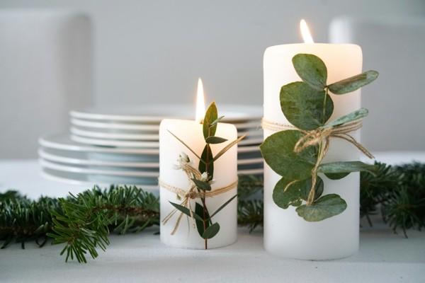 weiße stumpenkerzen mit eukalyptusblättern dekorieren