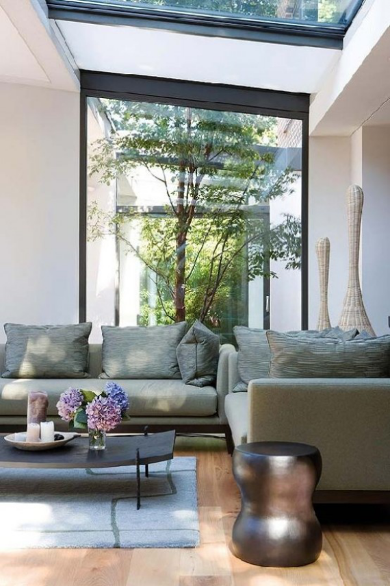 Innenhof stilvoll gestalten Minimalismus auf japanischer Art Sofa Kaffeetisch mit Vase Blumen im Hintergrund kleiner Garten drinnen und draußen im Einklang