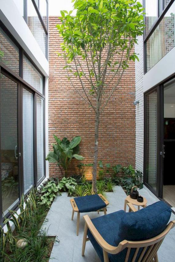 Innenhof stilvoll gestalten Ruheort ein Sessel Hocker viel Grün einladende Atmosphäre