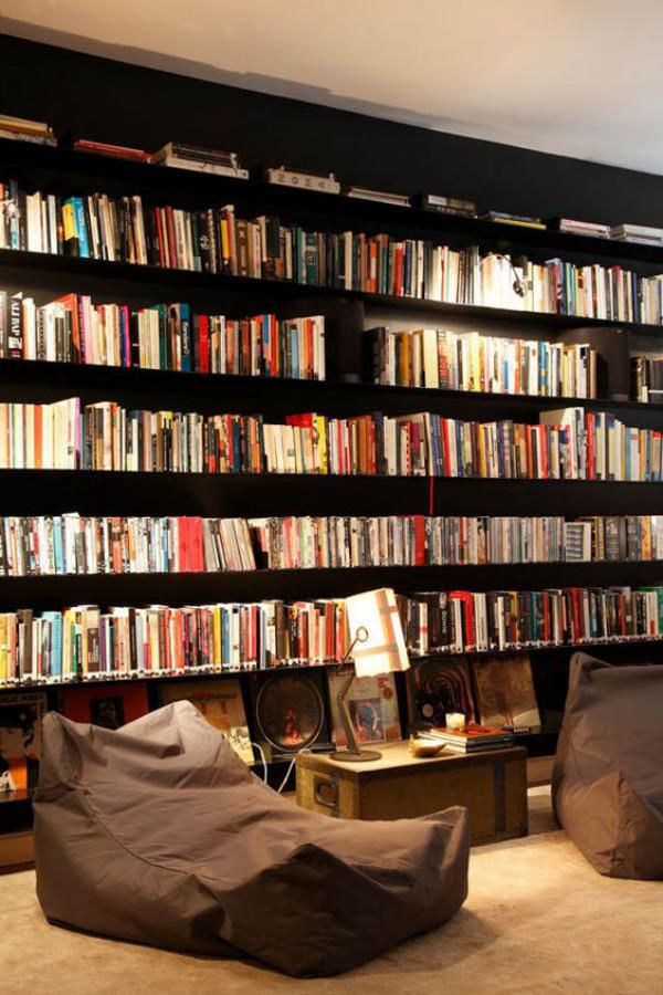Moderne Hausbibliothek Bücherwand zahlreiche Bücher bequeme Sitzpuffs