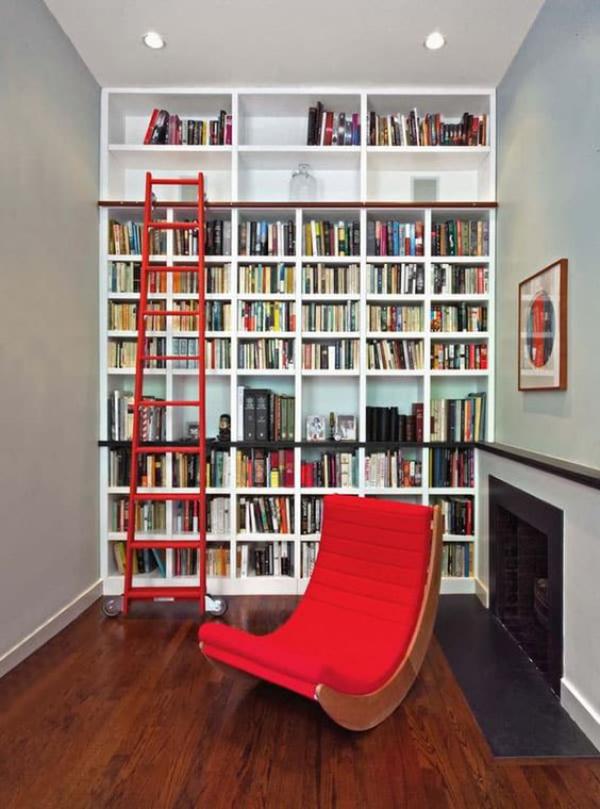 Moderne Hausbibliothek Kamin roter Schaukelstuhl Bücherwand deckenhoch Leiter