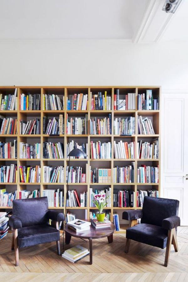 Moderne Hausbibliothek Leseecke zwei Sessel kleiner Tisch viele Bücher