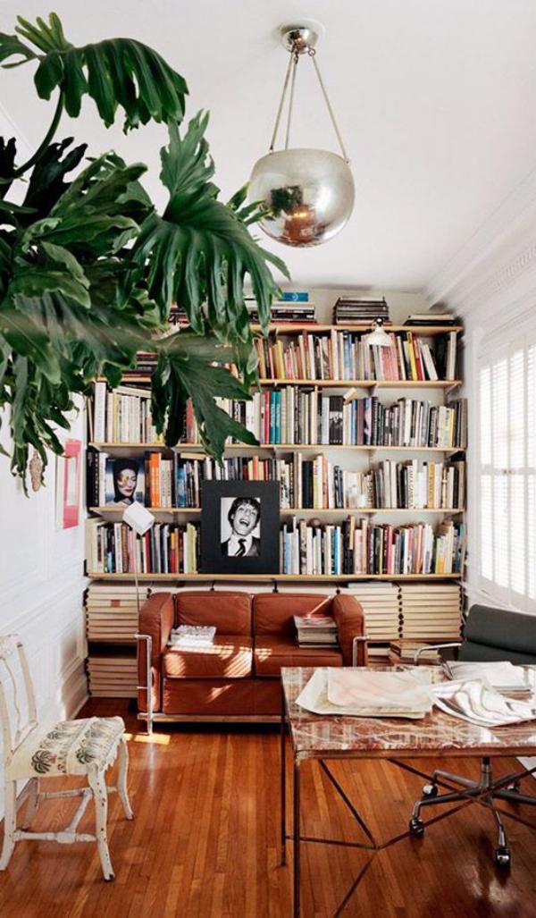 Moderne Hausbibliothek Sofa Tisch auf Rädern viel Holz warme Farben grüne Zimmerpflanze