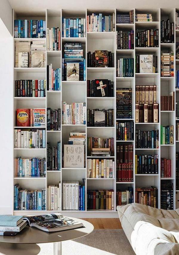 Moderne Hausbibliothek bequemes Sofa rechts runder Tisch viel natürliches Licht