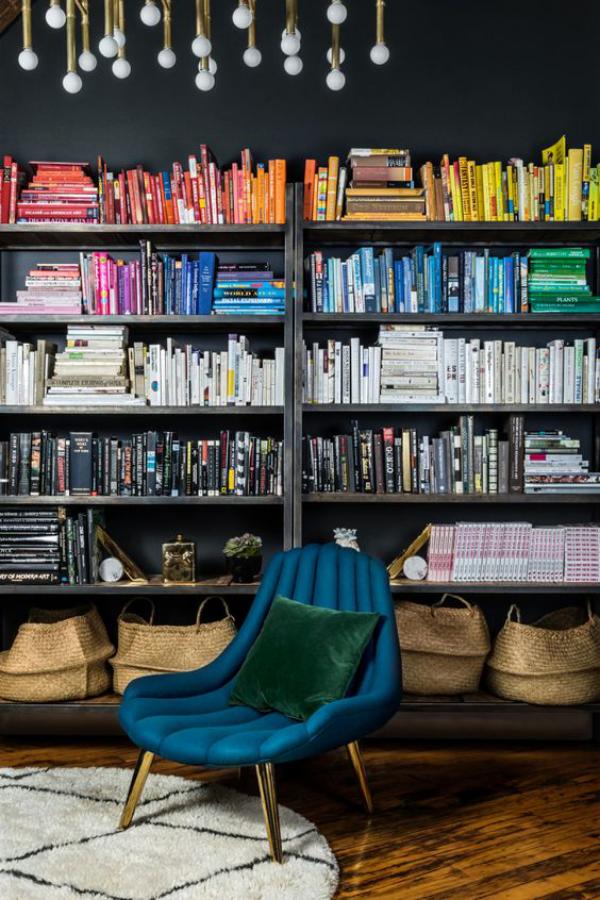 Moderne Hausbibliothek blauer Sessel Bücherwand Bücher anordnen nach Farben