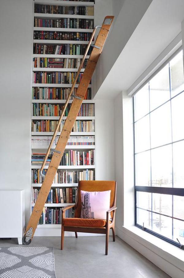 Moderne Hausbibliothek deckenhohe Fenster viel Licht Bücherwand Leiter