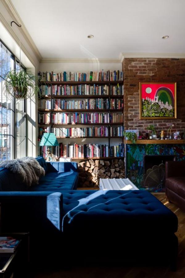 Moderne Hausbibliothek eine Wand mit Büchern neben Kamin komfortable Couch in Marineblau Licht