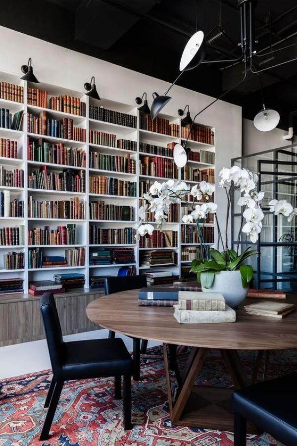 Moderne Hausbibliothek runder Tisch Sitzgelegenheiten weiße orchideen passendes Licht