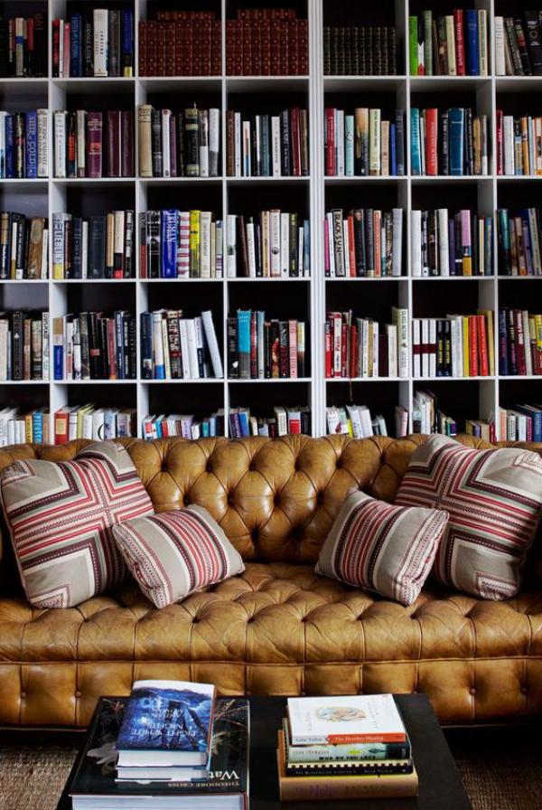 Moderne Hausbibliothek schickes Ledersofa einige weiche Kissen viele Bücher gemütlich