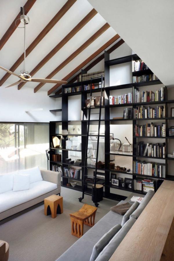 Moderne Hausbibliothek schwarze Bücherregale weiße Möbel Raum unter der Dachschräge