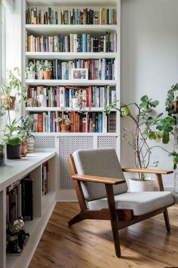 Moderne Hausbibliothek viel natürliches Licht Bücherregale an der Wand unter dem Fenster