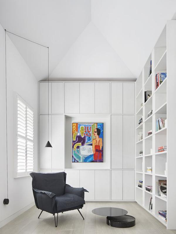 Moderne Hausbibliothek weißes Raumdesign buntes Wandbild als Akzent schwarzer Sessel