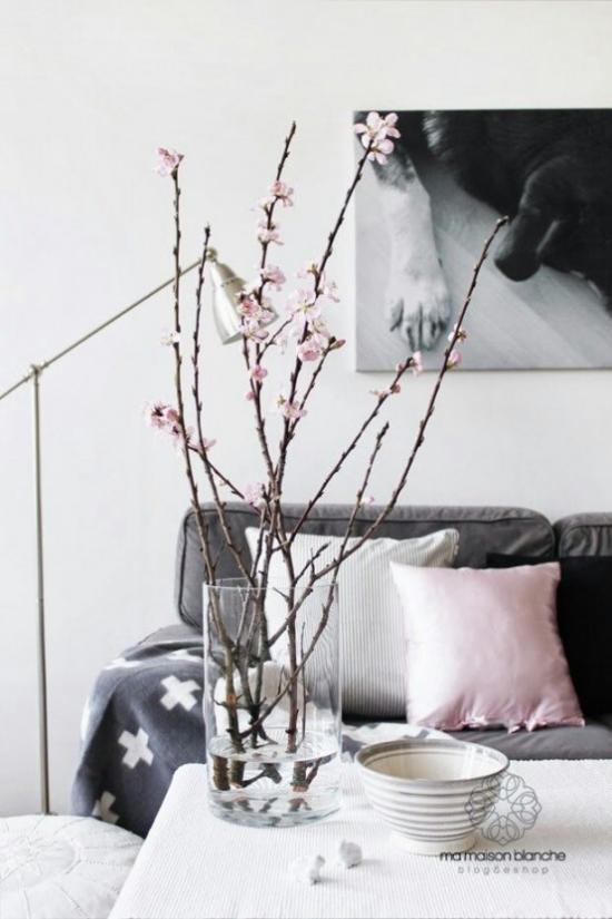 Frühlingsdeko mit Kirschblüten ein paar Kirschzweige im Glas im Wohnzimmer auf dem Kaffeetisch