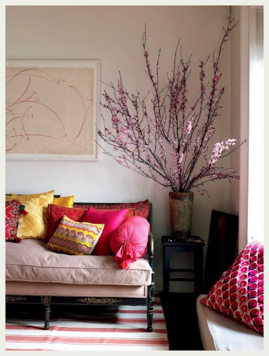 Frühlingsdeko mit Kirschblüten große Vase schön arrangierten Kirschzweige in der Ecke des Wohnzimmers Sofa bunte Wurfkissen