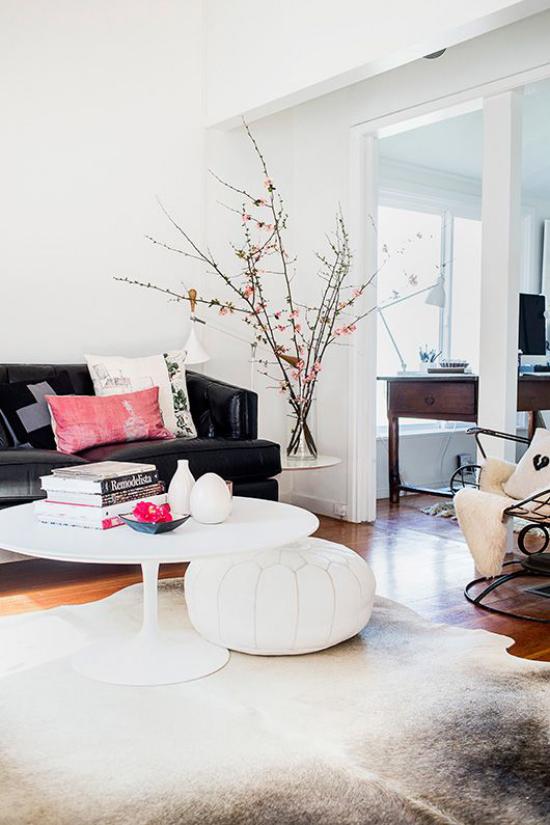 Frühlingsdeko mit Kirschblüten modernes Wohnzimmer in der Ecke neben der Couch Vase mit Kirschblüten stilvoll und romantisch