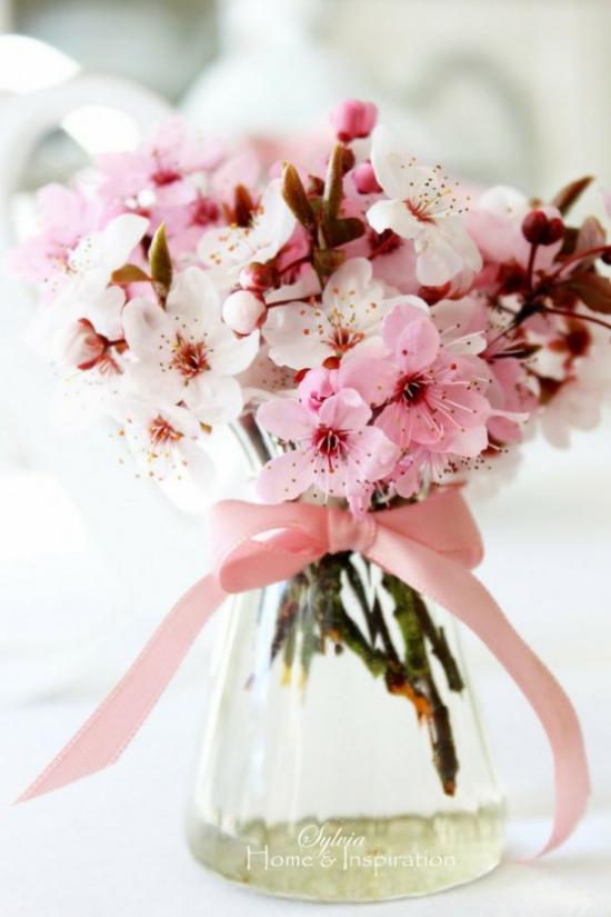 Frühlingsdeko mit Kirschblüten rosa Blüten im Glas rosa Schleife