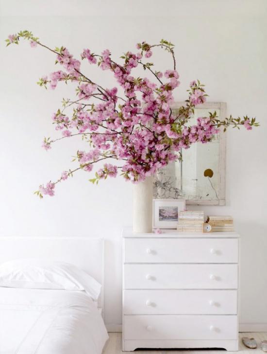 Frühlingsdeko mit Kirschblüten rosa Blüten in Vase weiße Kommode Wandspiegel