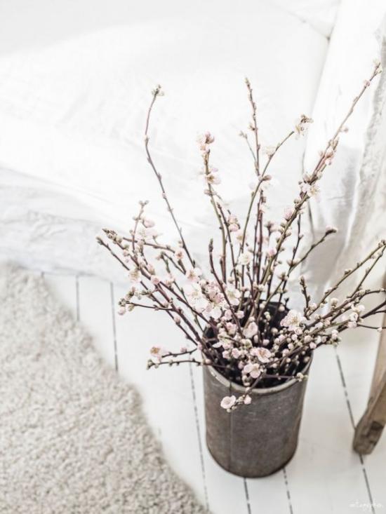 Frühlingsdeko mit Kirschblüten weiße Blüten im alten Gefäß im Wohnzimmer