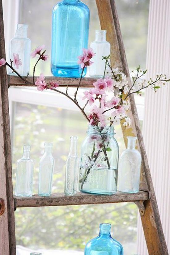 Frühlingsdeko mit Kirschblüten zwei drei Zweige rosa Blüten im Glas auf der alten Holzleiter