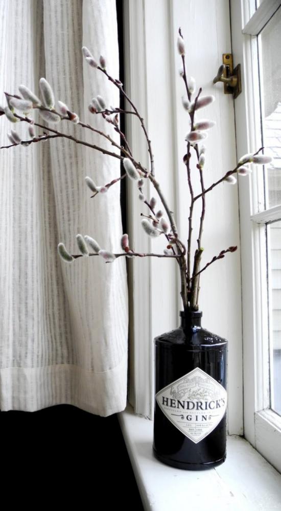Frühlingsdeko mit Weidenkätzchen Weidenzweige im Behälter aus schwarzem Glas auf der Fensterbank