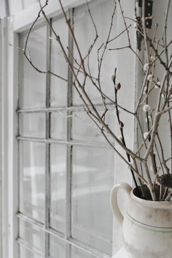 Frühlingsdeko mit Weidenkätzchen im Blumenbehälter draußen vor dem Fenster