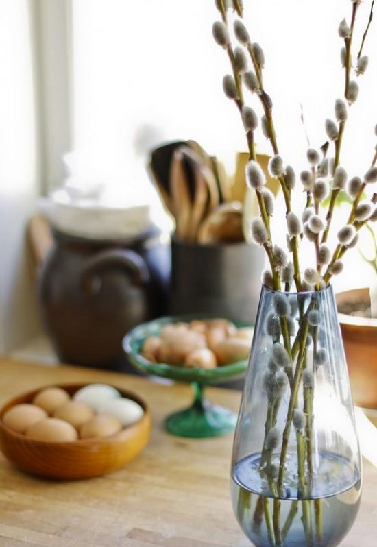 Frühlingsdeko mit Weidenkätzchen in Glasvase arrangiert Eier im Hintergrund