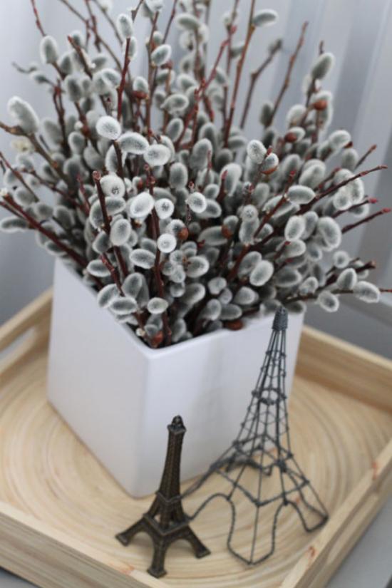 Frühlingsdeko mit Weidenkätzchen in der Vase arrangiert Eifelturm Souvenirs daneben
