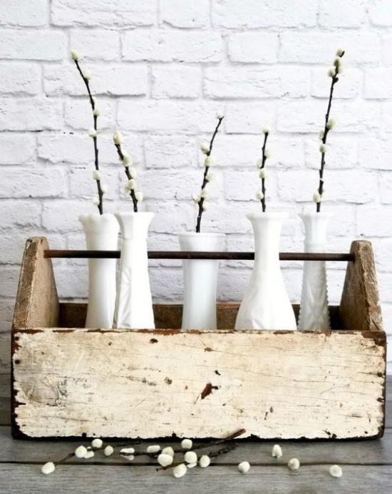 Frühlingsdeko mit Weidenkätzchen in kleinen weißen Vasen im Vintage Kasten