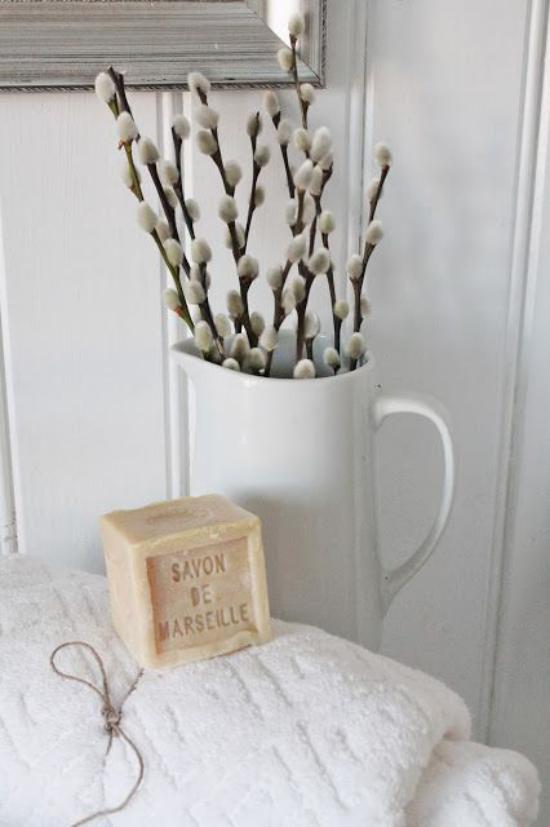 Frühlingsdeko mit Weidenkätzchen in weißer Gießkanne im Bad weiße Tücher Seife