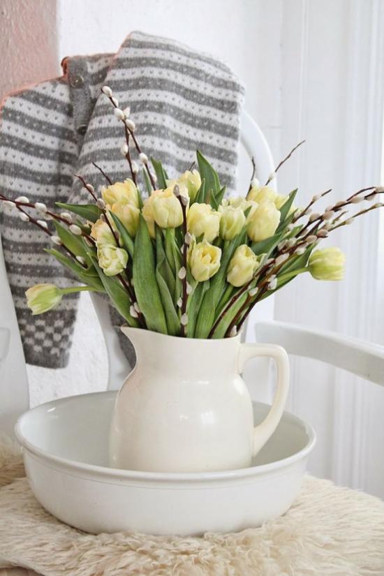Frühlingsdeko mit Weidenkätzchen in weißer Porzellankanne mit gelben Tulpen arrangiert