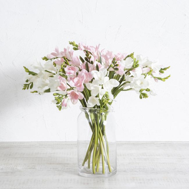 Freesien in Vase zarte Blüten in Weiß und Rosa lange dünne Stiele