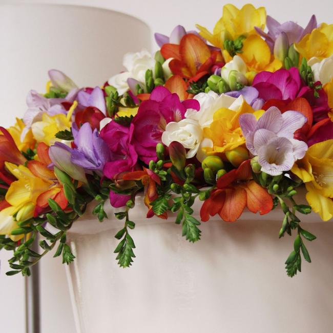 Freesien verschiedene gesättigte Farben auf dem Kaminsims arrangiert schöne Deko zuhause