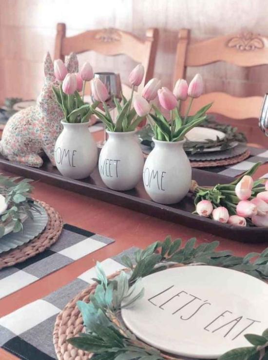 Küche frühlingshaft dekorieren auf Tablett drei weiße Porzellanvasen voll mit hellrosa Tulpen festlich dekorierter und gedeckter Tisch