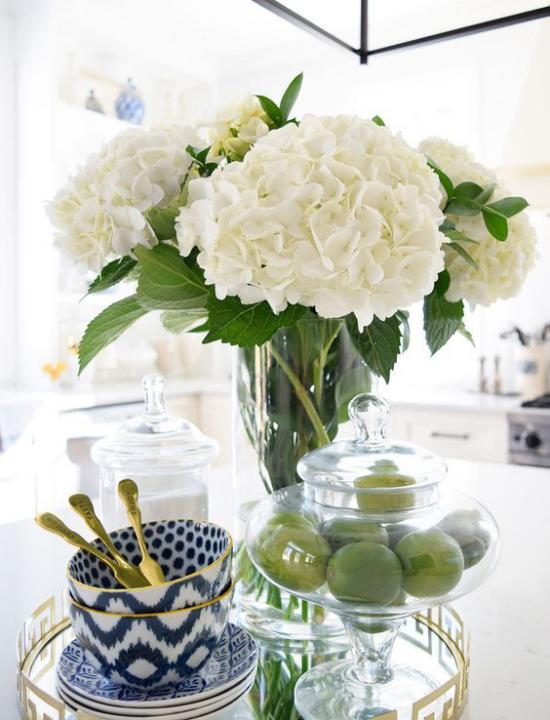 Küche frühlingshaft dekorieren weiße Hortensien in Vase aus Glas grüne Zitronen elegantes Kaffeeservice