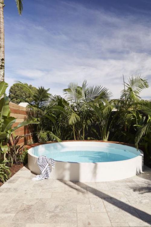 Runde Gartenpools Schwimmbecken im Hinterhof üppiges Grün Palmen als Sichtschutz Dschungel-Feeling