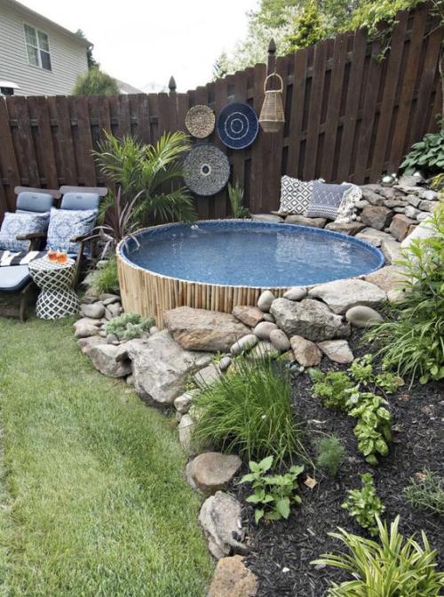 Runde Gartenpools im Hinterhof dekorativ verkleidet mit Steinen Zaun aus Holz Sitzecke daneben