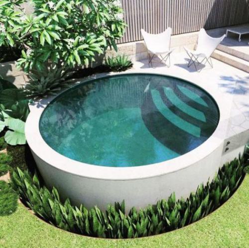 Runde Gartenpools kompakte Form Treppen zwei Liegestühle daneben viel Grün ringsherum