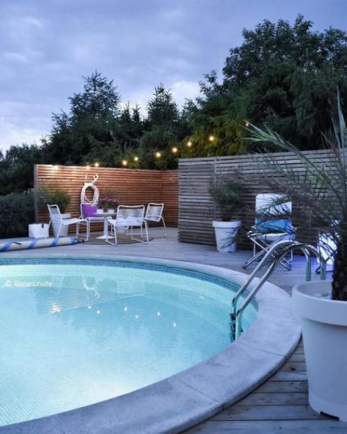 Runde Gartenpools modernes Schwimmbecken Treppe Lichterkette passende Beleuchtung Sitzecke Topfpflanzen