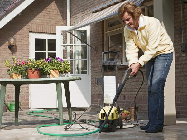 Saubermachen - Frau beim Terrassenplatten reinigen