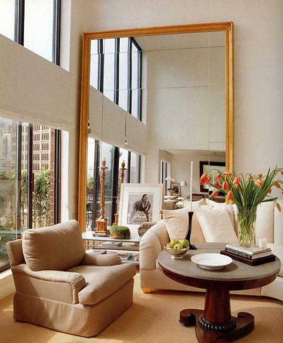 Wohnzimmer optisch erweitern übergroßer Spiegel neben dem Fenster reflektiert die Raumgestaltung und das Licht