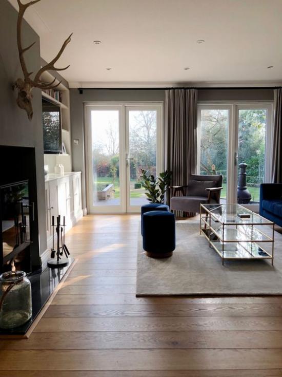Wohnzimmer optisch erweitern einladender und gemütlicher Raum Tageslicht hohe Fenster Beige dominiert dunkelblaue Akzente